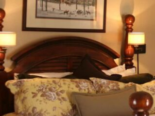 bed with brown headboard and picture above