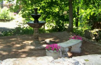 fountain, white bench and pink flowers