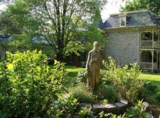 statue of lady with inn behind it