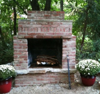 brick outdoor fireplace with fire blazing