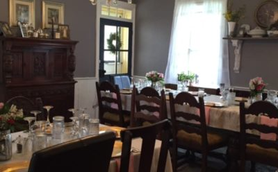 dining room with gray walls and brown furniture with dinnerware