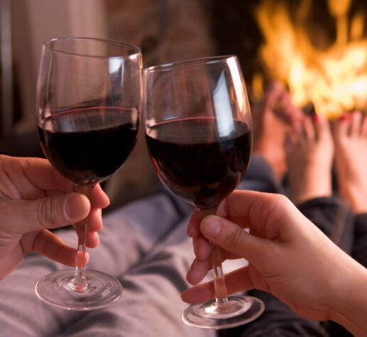people holding 2 glasses of wine before blazing fireplace