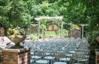 wedding setup with white chairs and arbor