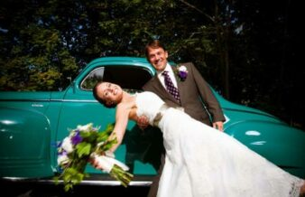 bride and groom in front of aqua colored car