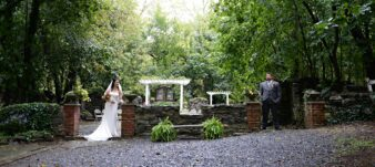 bride and groom standing near stone wall