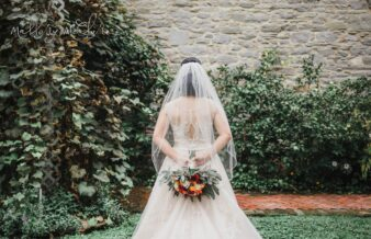 bride holding floral bouquet behind back