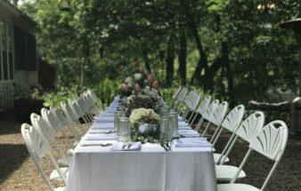 table set outdoors with white tablecloth and flowers