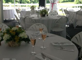 tables under tent set with glasses of champagne