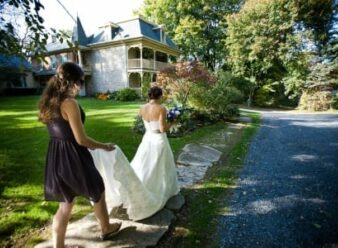 girl holding train of bride walking before her