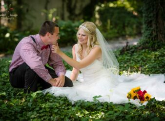 bride sitting in ivy with her hand on groom's chin