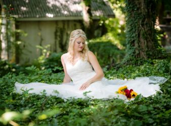 bride sitting on ivy looking at red and yellow flowers