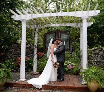 bride and groom under arbor