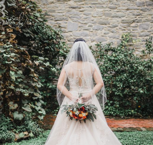 bride holding red floral bouquet behind back