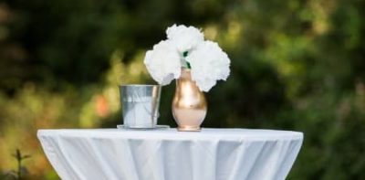 white table holding vase of white flowers