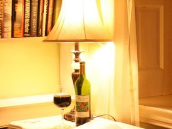 brightly lit lamp with book and glass and bottle of wine