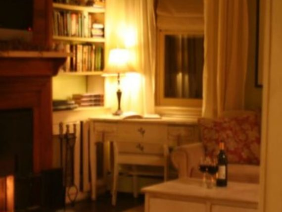 room with brightly lit lamp and bottle and glass of wine